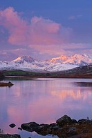 Wales, Conwy, Capel Curig. Llynnau Mymbyr lake and snow capped mountains beyond in the Dyffryn Mymbyr valley.