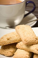 , , . Scottish shortbread biscuits with cup of tea in background.