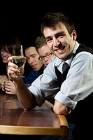Man smiling for the camera at bar with people behind