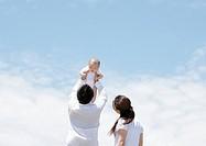 Parents and child under blue sky