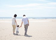 Parents and child walking on beach