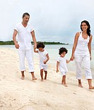 Beautiful family walking on the beach while on vacations
