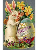 A vintage Easter postcard of a rabbit painting an egg