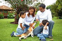 happy family at home outdoors looking after their dog _ togetherness concept