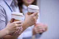 Colleagues holding drink for coffee break