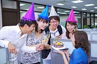 Colleagues wearing headwear and toasting for celebrating
