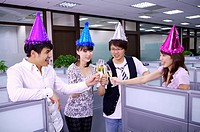 Four colleagues wearing party hats and celebrating together