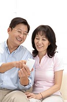 Couple, Couple looking at the mobile phone together and smiling happily (thumbnail)
