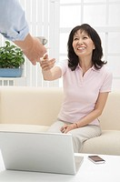 Couple, Woman sitting on sofa, reaching hand and smiling happily
