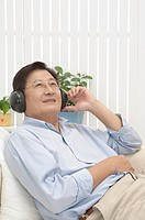 Man lying on sofa and listening music with smile