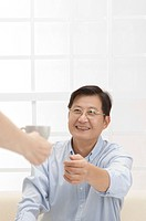 Couple, Husband reaching hand to take a cup of tea from wife and smiling