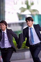 Two businessmen holding briefcase and running together