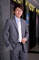 Young businessman standing and looking at the camera with smile (thumbnail)