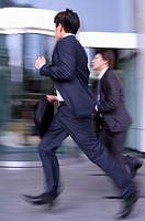 Two businessmen running together