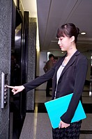 Young woman holding document folder and pressing elevator
