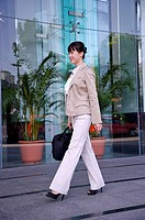 Young woman holding briefcase and walking