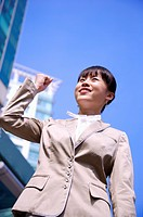 Young woman looking up with fists up and smiling