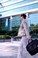 Young businesswoman holding briefcase and walking