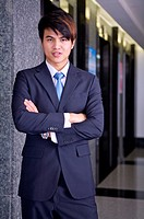 Young businessman standing with hands on chest and smiling at the camera