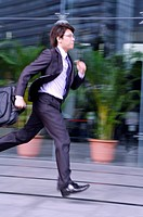 Young businessman holding briefcase and running fast