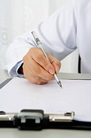 Doctor writing on the clipboard with a pen