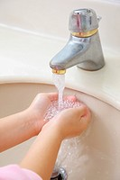 Little girl's washing hands under faucet