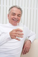 Domestic Life, a Senior_aged man holding a glass of drink and smiling
