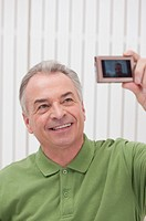 Domestic Life, a senior man taking picture of himself and smiling (thumbnail)