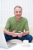 Domestic Life, a senior man holding mobile phone and smiling at the camera