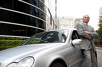 Senior businessman standing beside the car and looking up with smile