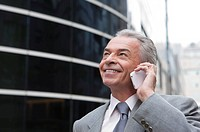 Senior businessman using mobile phone and looking up with smile