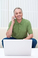 Domestic Life, a senior man using mobile phone and smiling at the camera