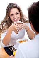 Couple at the table eating breakfast isolated over white