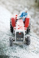 Toy tractor with driver covered in ice cystals