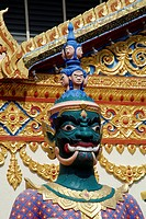 Head and shoulders of statue of fierce green faced temple guardian with heads of dead adverseries on helmet spike ornate decoration on wall and eaves ...