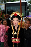 Severe looking Sasak bride in dark clothing with gold trim wearing gold chain with coins amd gold earrings looks to left as she walks in tradional Mus...