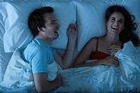 Couple lying together in bed laughing