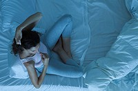 Woman sitting in bed taking temperature