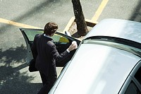 Businessman getting into car (thumbnail)