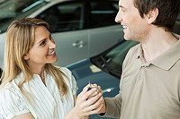 Couple in car dealership showroom with key to new car