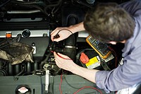 Mechanic diagnosing car engine problem