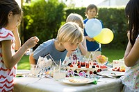 Boy blowing candles on birthday cake at outdoor birthday party