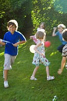 Children playing outdoors with balloons