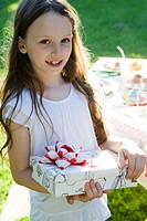 Girl at birthday party holding wrapped gift