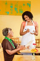 African American woman taking customer´s order in cafe