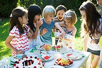 Girl opening gift at birthday party as friends watch