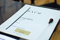 Conductors musical score with baton on stand