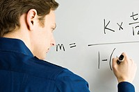 Man writing equation on whiteboard