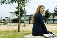 Female student sitting on bench on school campus