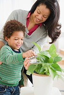Mixed race mother helping son water plants